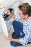Technician repairing a washing machine Stock Image