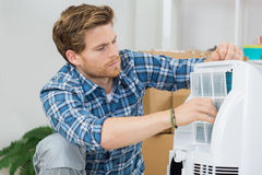 Technician repairs air conditioning unit. Technician repairs an air conditioning unit Royalty Free Stock Image
