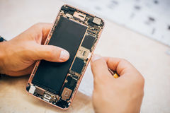 Technician repairs and inserts sim memory card on mobile phone Royalty Free Stock Photography