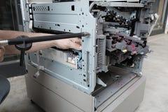 Technician repairs photocopier. Broken  open Stock Photos
