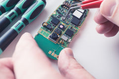 Technician replace component on damaged smartphone. By pincers. close-up shot Royalty Free Stock Photos
