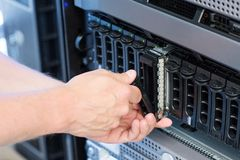 IT technician Replace Harddrive. It engineer / technician working in a data center. Disk cabinet and servers Stock Photography