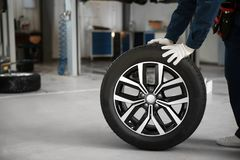 Technician rolling car wheel in automobile repair shop closeup. Space for text royalty free stock photography