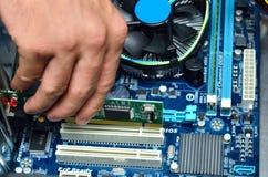 Technician's hand assembling personal computer Stock Photos