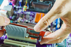 Technician's hands fixing mainboard. Technician's hands fixing computer mainboard Stock Photos