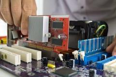 Technician's hands Installing VGA card. Installing VGA card on computer mainboard Royalty Free Stock Photography