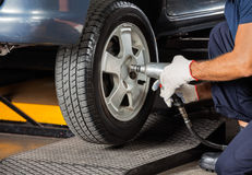 Technician Screwing Car Tire With Pneumatic Wrench Stock Images