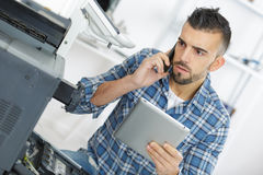 Technician seeking help on phone while repairing printer Royalty Free Stock Photography