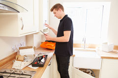 Technician servicing boiler in kitchen using tablet computer Stock Image