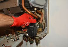 Technician servicing the gas boiler. Repairman fixing a gas water heater boiler royalty free stock photography
