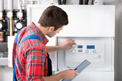 Technician servicing heating boiler Royalty Free Stock Photos