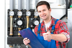 Technician servicing heating boiler. Technician servicing the gas boiler for hot water and heating Royalty Free Stock Photography