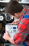 Technician servicing heating boiler Stock Image