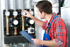 Technician servicing heating boiler. Technician servicing the gas boiler for hot water and heating Royalty Free Stock Images