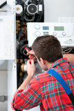 Technician servicing heating boiler. Technician servicing the gas boiler for hot water and heating Stock Photos