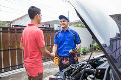 Technician shake hand with customer. Car technician shake hand with customer in the house Royalty Free Stock Photos