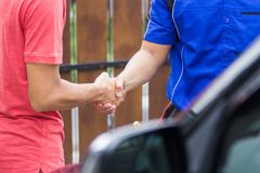 Technician shake hand with customer. Close up of car technician shake hand with customer in the house Stock Images