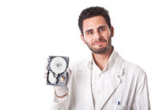 Technician showing hard disk. A technician wearing lab coat holding an hard disk drive Stock Photos