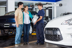 Technician Showing Metallic Alloy. Male technician showing metallic alloy to couple at auto repair shop Stock Images