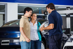 Technician Showing Metallic Hubcap To Couple Stock Photography