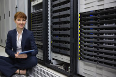 Technician sitting on floor beside server tower using tablet pc Royalty Free Stock Images