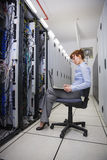 Technician sitting on swivel chair using laptop to diagnose servers Stock Images