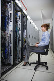 Technician sitting on swivel chair using laptop to diagnose servers Stock Image