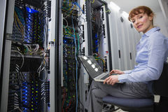 Technician sitting on swivel chair using laptop to diagnose servers Royalty Free Stock Image