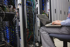Technician sitting on swivel chair using laptop to diagnose servers Royalty Free Stock Images