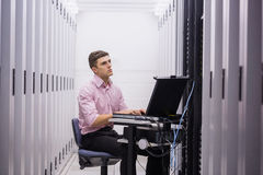 Technician sitting on swivel chair using laptop to diagnose servers Stock Photography