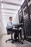 Technician sitting on swivel chair using laptop to diagnose servers. In large data center Royalty Free Stock Photography