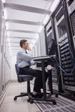 Technician sitting on swivel chair using laptop to diagnose servers Royalty Free Stock Photography