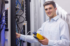 Technician smiling at camera while fixing server. In large data center Royalty Free Stock Photo