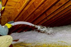 Technician spraying blown Fiberglass Insulation between Attic Trusses foam insulation construction foam from the gun to the roof. Technician spraying blown stock image