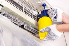 Technician spraying chemical water onto air conditioner grid to. Technician spraying chemical water onto air conditioner coil to clean and disinfect stock photo