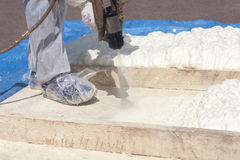 Technician spraying foam insulation using Plural Component Spray Gun. Royalty Free Stock Image