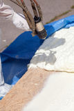 Technician spraying foam insulation using Plural Component Spray Gun. Stock Photography