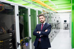 Technician standing with arms crossed in a server room. Portrait of technician standing with arms crossed in a server room Stock Photos