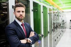 Technician standing with arms crossed in a server room. Portrait of technician standing with arms crossed in a server room Stock Image