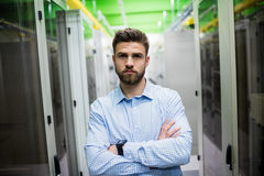 Technician standing with arms crossed in a server room. Portrait of technician standing with arms crossed in a server room Royalty Free Stock Photography
