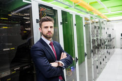 Technician standing with arms crossed in a server room Stock Photos