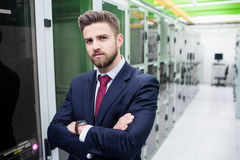 Technician standing with arms crossed in a server room. Portrait of technician standing with arms crossed in a server room Royalty Free Stock Photo
