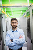 Technician standing with arms crossed in a server room. Portrait of technician standing with arms crossed in a server room Royalty Free Stock Images