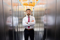 Technician standing with arms crossed in a server room Stock Image