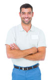 Technician standing arms crossed on white background. Portrait of smiling male technician standing arms crossed on white background Stock Photo