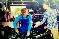 Technician standing with customer in shop Royalty Free Stock Photo