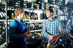 Technician standing with customer in shop. Happy male technician standing with customer in shop with motorcycles. Focus on the right man Royalty Free Stock Photo