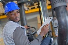 Technician standing driving vehicle. Technician standing driving a vehicle Royalty Free Stock Photography