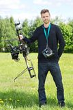 Technician Standing With UAV. Portrait of confident technician standing with UAV helicopter and remote control in park royalty free stock photo