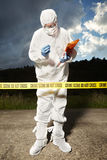 Technician in sterile suit behind barrier tape Royalty Free Stock Photo